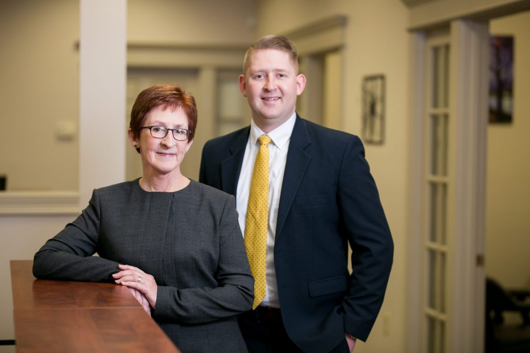 Attorneys Abbe and Ryan McLane posing together at the front desk of their law office.