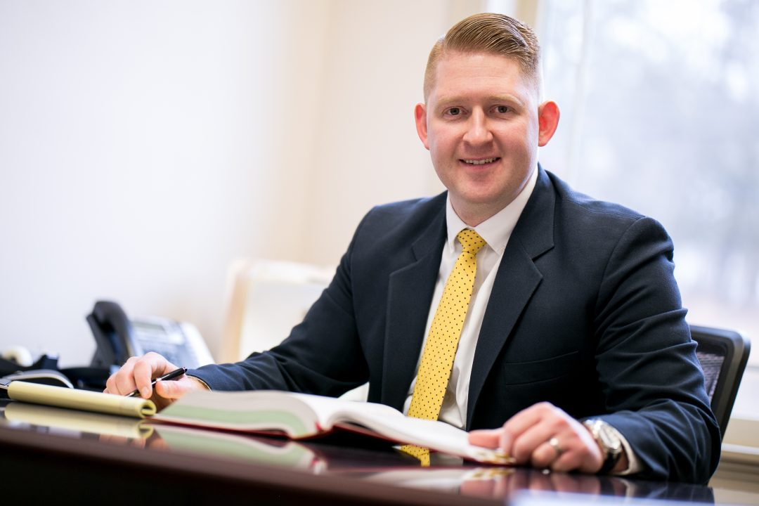 Ryan McLane smiling while working at his desk.