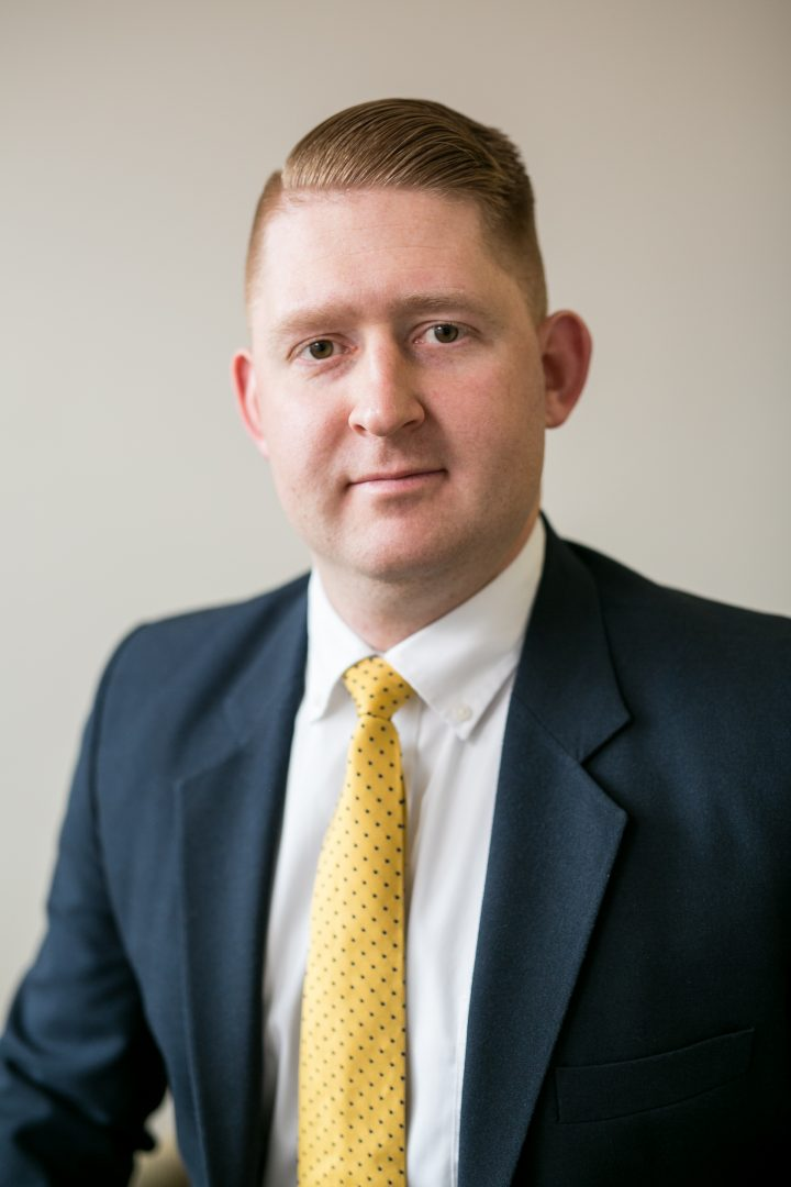 Portrait of Attorney Ryan McLane, wearing a navy suit and yellow tie.