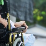 Photo of an aged person's hand on the arm of a wheelchair and their cargiver's hand pushing the wheelchair.