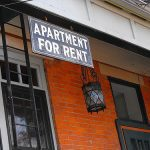 Apartment for Rent sign outside a brick multi-family home.