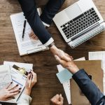 An above view of two people shaking hands across a table strewn with business documents.